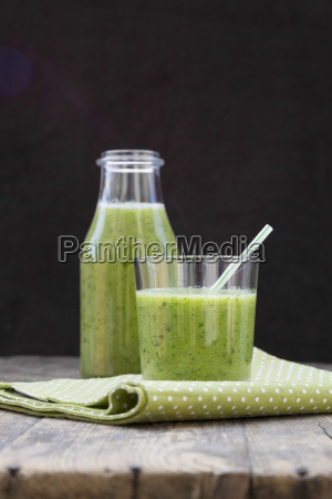 glass bottle and glass of green
