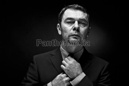 portrait of mature man adjusting tie