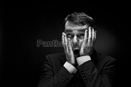 mature man gesturing against black background
