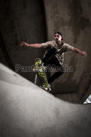 skateboarder performing trick at skateboard park