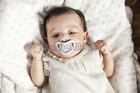 baby girl with pacifier in crib