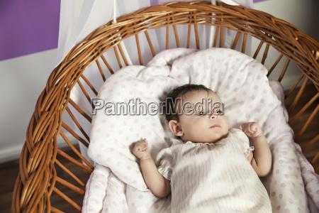 baby girl lying in wicker crib