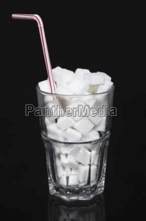 glass of sugar cubes with drinking