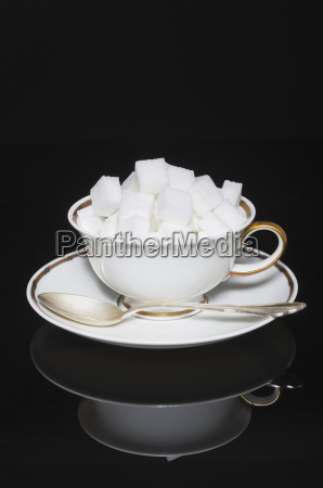 cup of sugar cubes with saucer