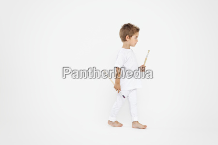 toddler holding paint brushes