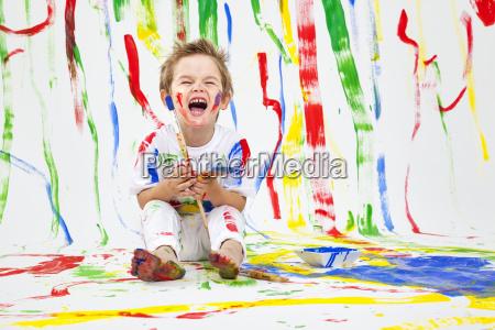 toddler having fun with green paint