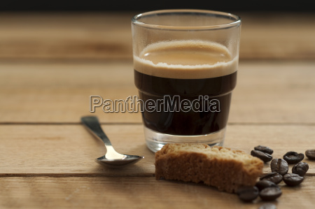 glass of espresso with roasted coffee