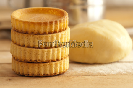 dough with baking tartlets on wooden