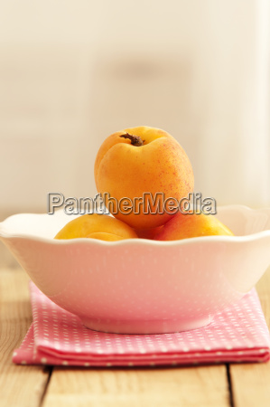 bowl of apricots on wooden table