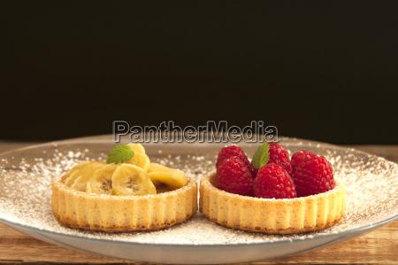 banana and raspberry tartlets on plate