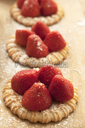 strawberry tartlet on chopping board close