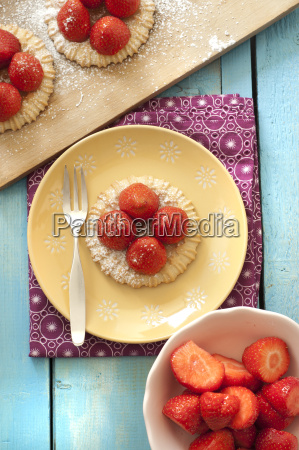 strawberry tartlets on plate besides bowl