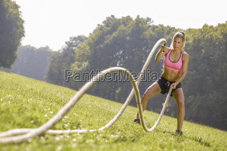 young woman training with workout ropes