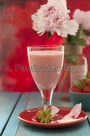 glass of strawberry shake with flowers