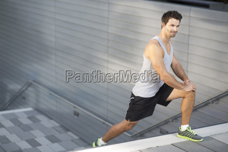 sportsman doing stretching exercises on a