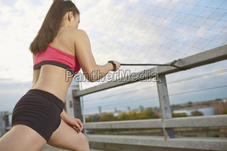 young female asian sportswoman doing stretching