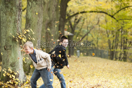 two boys throwing autumn leaves in