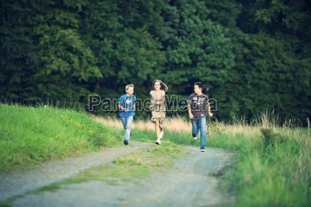 three siblings running side by side