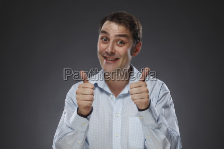portrait of smiling man with thumbs
