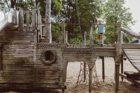 little boy standing on wooden playground