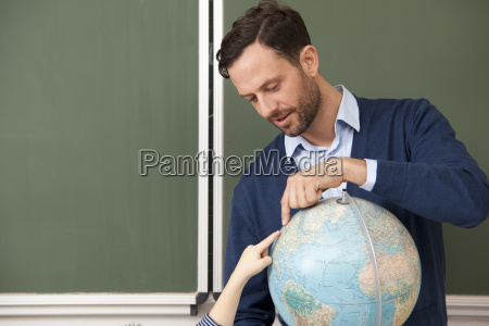 teacher and pupil pointing at globe