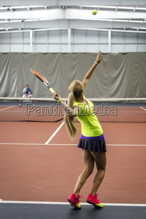 young woman playing tennis in an