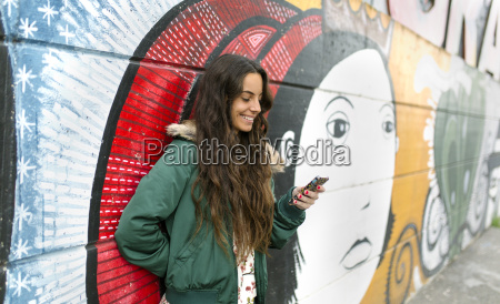 smiling young woman looking at cell