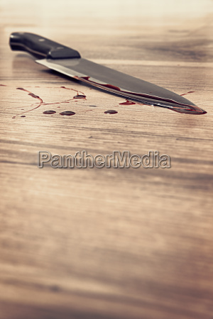 blood stained knife on wooden floor