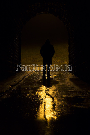 unrecognisable man in tunnel at night