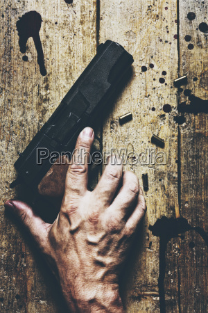 mans hand revolver and cartridges on