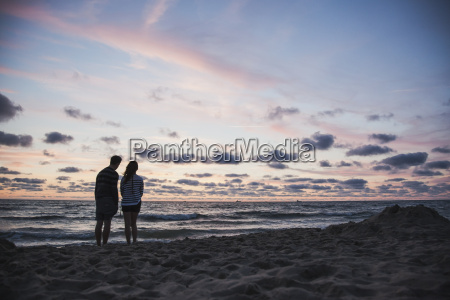 silhouette of teenage couple standing on