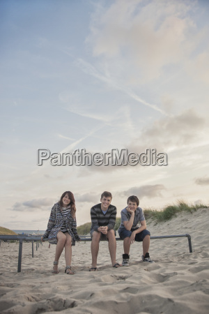 netherlands three smiling teenagers sitting in