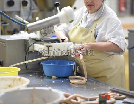 worker in a factory producing sausages