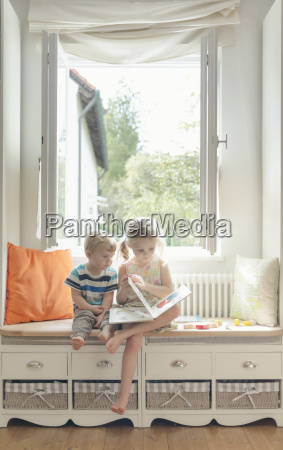 brother and sister reading a picture