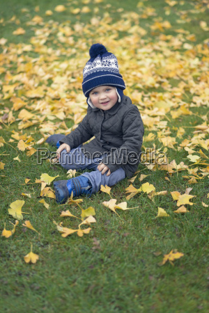 smiling toddler sitting on a meadow