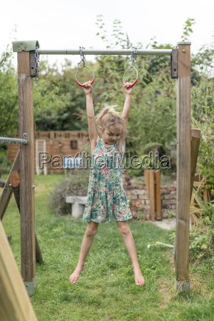 little girl hanging on gymnastic rings