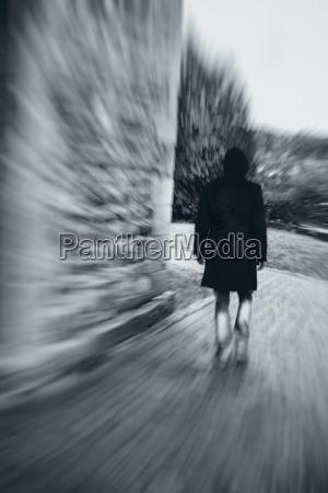man with hooded jacket walking at