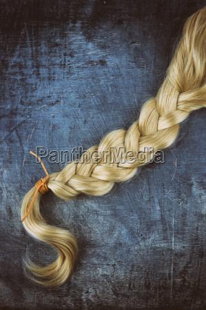 blond braid on wooden background