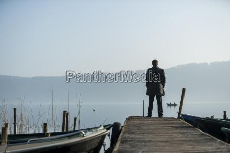 man standing on wooden boardwalk watching