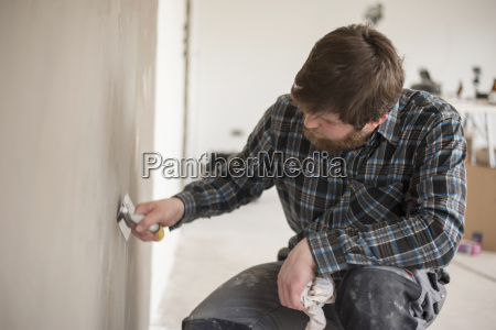 man testing plastered wall