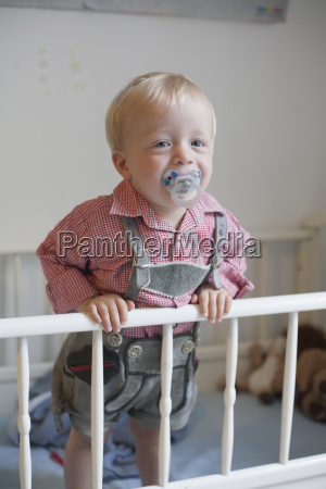 toddler with pacifier staying in his