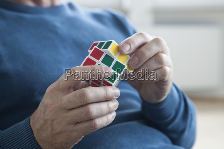 man playing with rubiks cube