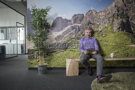 businessman in office using tablet sitting