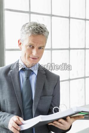 germany portrait of businessman holding file