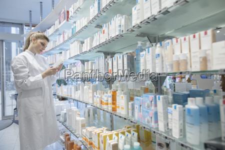 young pharmacist in pharmacy choosing medication