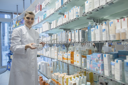 young pharmacist in pharmacy choosing medication