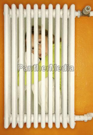 girl crouching behind a heater