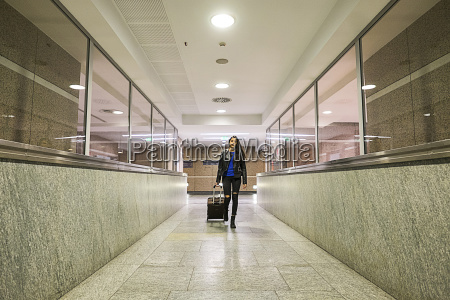 young woman with rolling suitcase walking