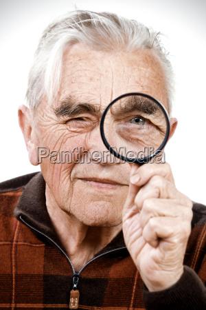 portrait of senior man holding magnifying