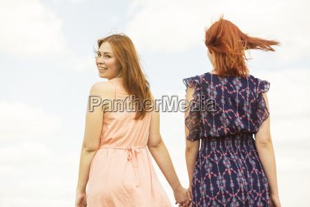two friends walking hand in hand